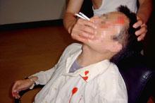 酷刑演示:将两根烟同时点着插入法轮功学员的鼻孔,把嘴捂住。熏呛、窒息极为痛苦