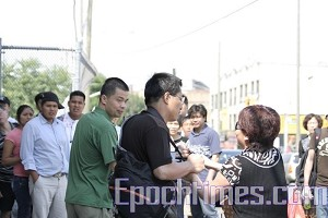 The woman who slapped John Yu on June 15 grabs the camera of Mr. Xue. (The Epoch Times)