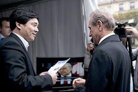 巴黎市长德拉诺埃在法轮功展区听取法国法轮功协会负责人的介绍
