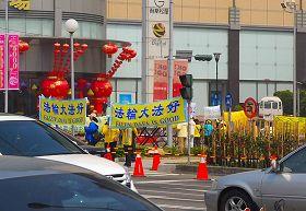 '法轮功真相横幅向着陈云林活动的嘉义市耐斯王子饭店展现在车潮汹涌的忠孝路上'