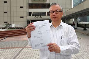 香港神韵晚会主办方发言人于二零一一年三月九日在高等法院外展示裁定主办方胜诉的判决书。