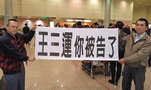 """""""你被告了""""--中共人权恶棍安徽省长王三运四月十八日来台,法轮功学员在机场中拉横幅"""