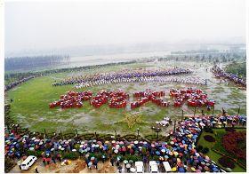 """一九九九年四月十一日,武汉七千学员排""""法轮大法""""字形,雨中听交流。"""