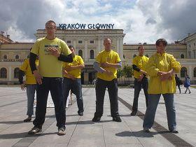 法轮功学员在克拉科夫中心火车站广场上炼功,满天乌云悄然散去