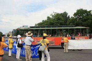 游览车上的游客对游行的法轮功学员招手致意