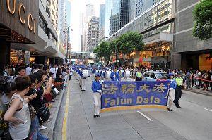 法轮功反迫害游行队伍由天国乐团领头,步入广东道,马路两旁站满了观看和拍照的市民及游客。