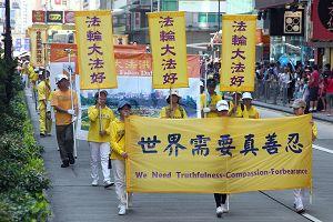 游行队伍展示法轮功真相横幅及海报。