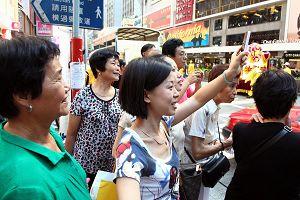 市民及游客纷纷拿起手机、相机,拍摄游行的盛况。