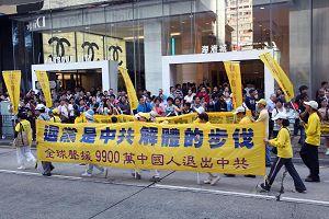 """游行人士排成方阵,手持""""退党是解体中共的步伐""""横幅,在繁忙的市区经过。"""
