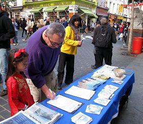 带着女儿在反迫害征签表上签字的英国先生