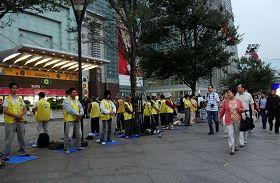 台湾法轮功学员长期在台湾各景点讲真相及洪法,图为大陆观光客观看法轮功学员在台北一零一大楼前炼功。