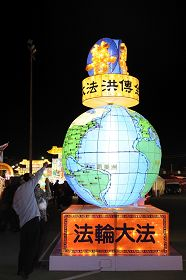 法轮功学员展示主题为「大法弘传全世界」的二层楼高的旋转大地球