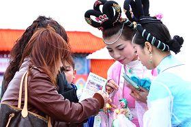 民众除了拿着仙女队仙女送的莲花,同时也拿法轮功简介。