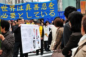 """日本法轮功学员游行纪念""""四•二五"""",经过东京繁华街头,许多市民驻足观看"""