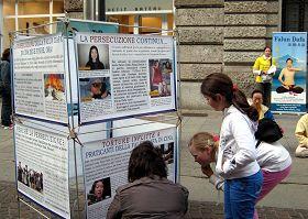 一位意大利母亲蹲在展板前,向她的孩子解释在图片上的迫害真相