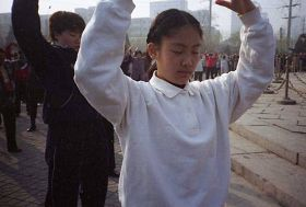一九九九年四月初,几个炼功点的近千名法轮功学员在沈阳和平广场晨炼——炼功人群中的小学生。