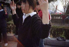 一九九九年四月初,几个炼功点的近千名法轮功学员在沈阳和平广场晨炼——炼功人群中的大学生,学员身前的红光,旋转的法轮。