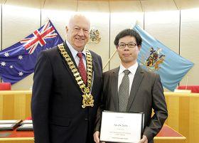 市长(左)在市政府议员会议上为法轮功团体代表颁奖