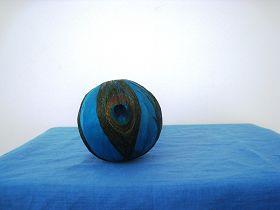 孔雀翎球直径约10cm(制作第一步是把白色泡沫做的圆球去掉多余部分,磨平,然后涂上黄胶,把染上蓝色的可能是鹅毛粘在球上,再把四个孔雀毛涂上胶粘上)