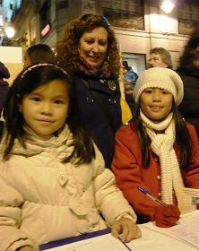 一位女士与自己领养的两个中国女孩一同签名支持法轮功