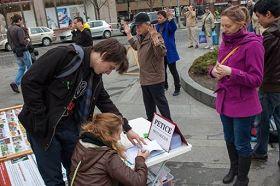 民众观看法轮功真相展板后,签名支持反迫害,抗议中共暴行
