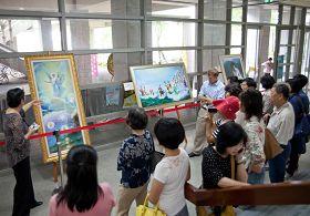 '高雄大学邻近的英文学习社团特别停课一次,全体师生二十多人相约观赏美展,导览人员正用英文解说画作。'
