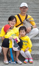工程师、教师夫妇带着三位年幼的小娃儿,一家五人很开心一起参加庆祝游行活动。