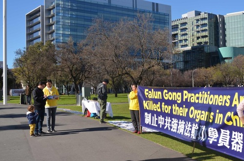 Para pejalan kaki menonton kegiatan dan menandatangani petisi yang mendukung penuntutan terhadap mantan pemimpin Tiongkok Jiang Zemin