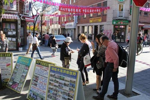 Pejalan kaki membaca spanduk dan menandatangani petisi untuk mendukung aksi damai praktisi menentang penganiayaan.