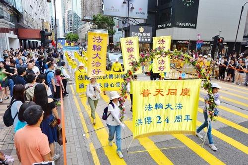 Wisatawan dan penduduk Hong Kong mengambil video dan gambar pawai akbar praktisi Falun Gong.