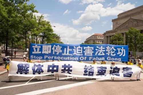 """Spanduk putih di depan bertulisan, """"Bubarkan Partai Komunis Tiongkok dan Hentikan Penganiayaan."""""""