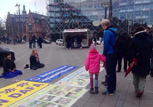 Praktisi Falun Gong bermeditasi di depan spanduk dan poster