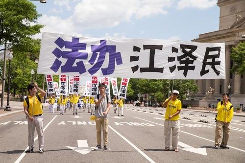 """Spanduk besar bertulisan """"Adili Jiang Zemin."""" Jiang Zemin adalah mantan pemimpin Partai Komunis Tiongkok yang melancarkan penganiayaan terhadap Falun Gong pada tahun 1999."""