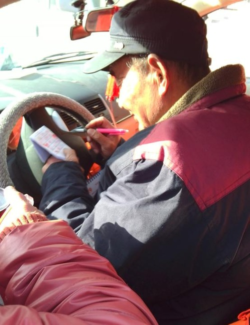 Seorang sopir taksi menandatangani petisi menyerukan untuk menuntut mantan pemimpin Tiongkok Jiang Zemin.