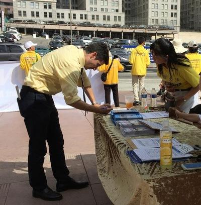 Orang lewat menandatangani petisi - untuk menghentikan penyiksaan