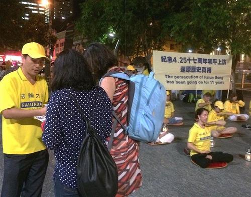 Para pejalan kaki berhenti untuk mempelajari tentang Falun Gong