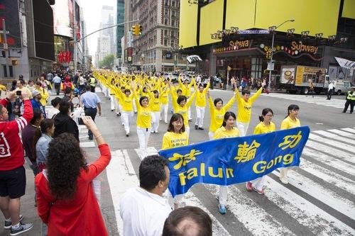 Praktisi memeragakan latihan Falun Gong selama pawai.