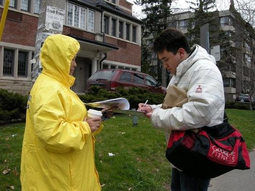 Ian King, warga setempat, mengambil foto kegiatan dan menandatangani petisi untuk mengecam kebrutalan dari penganiayaan