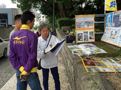 Seorang Praktisi Falun Gong berbicara dengan dua pemuda tentang tuntutan hukum terhadap Jiang Zemin.