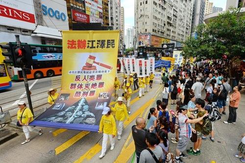 "Spanduk besar berbunyi: ""Adili Jiang Zemin karena kejahatan terhadap kemanusiaan, genosida dan penyiksaan,"""