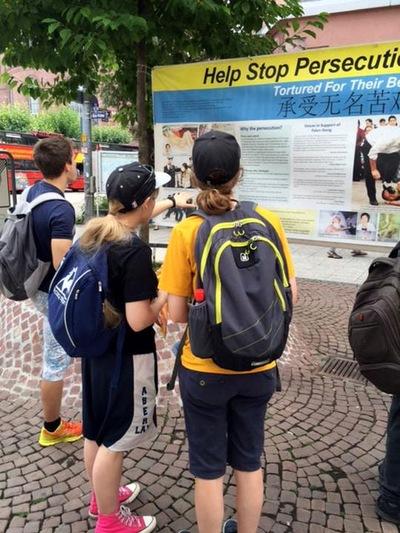Pengunjung membaca poster tentang penganiayaan di Tiongkok