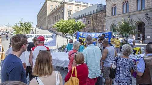 Para pengunjung melihat praktisi mengekspos penganiayaan oleh PKT di Coin Square