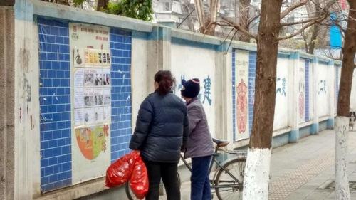 Dua orang yang lewat membaca poster di Kota Wuhan, Provinsi Hubei.