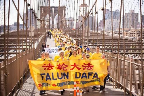 Praktisi Falun Dafa di Kota New York berjalan di Jembatan Brooklyn di Kota New York pada tanggal 15 Mei 2015.