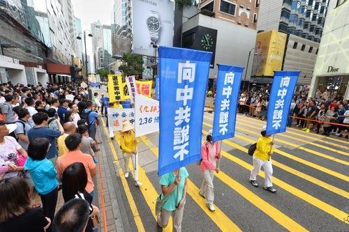Spanduk di bagian ketiga dan keempat pawai, memperlihatkan penganiayaan dan menyerukan orang-orang Tiongkok untuk meninggalkan partai komunis.