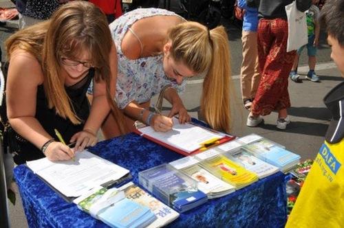 Dua pengunjung menandatangani petisi di kegiatan dekan Kedutaan Besar Tiongkok di Paris pada 22 Juli