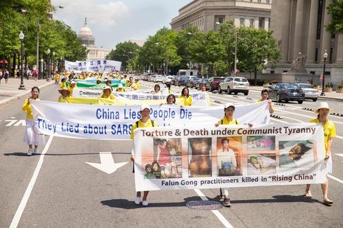 Spanduk di depan memperlihatkan gambar praktisi yang disiksa karena kepercayaan mereka kepada Falun Gong.