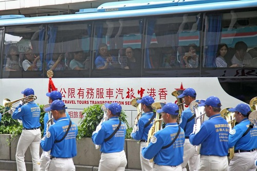 Wisatawan Tiongkok di bus tur mengambil gambar saat Tian Guo Marching Band lewat.