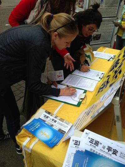 Dua wanita menandatangani petisi untuk menuntut Jiang Zemin