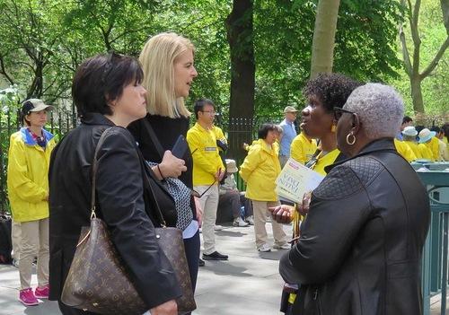 Para pejalan kaki mendengar tentang Falun Gong dan penindasan di Tiongkok
